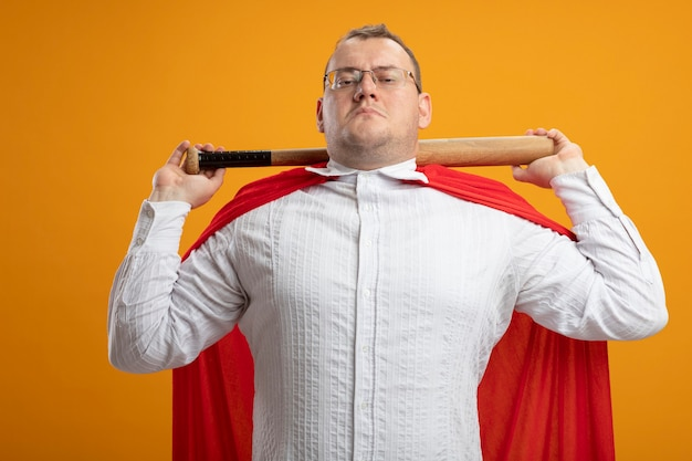 Zelfverzekerde volwassen slavische superheld man in rode cape bril met honkbalknuppel achter nek geïsoleerd op oranje muur