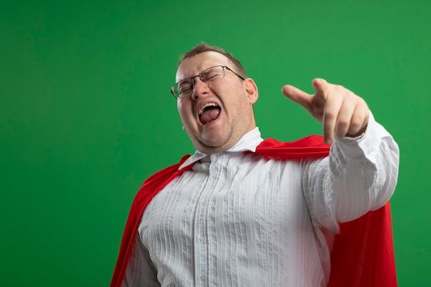 Zelfverzekerde volwassen slavische superheld man in rode cape bril wijzend met gesloten ogen geïsoleerd op groene muur met kopie ruimte