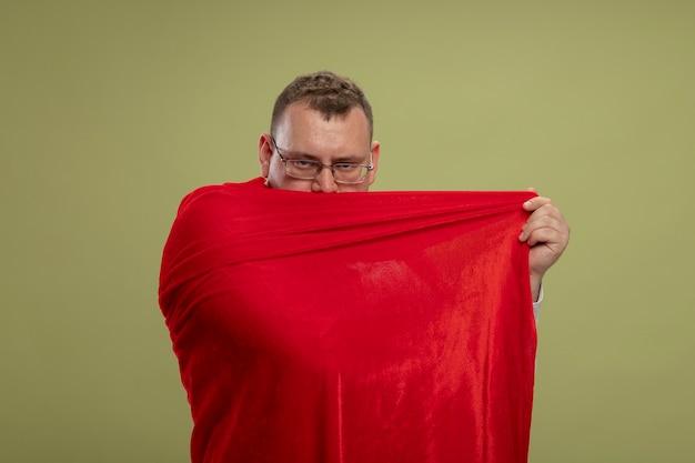Zelfverzekerde volwassen slavische superheld man in rode cape die een bril draagt die zichzelf bedekt met cape van erachter geïsoleerd op olijfgroene muur