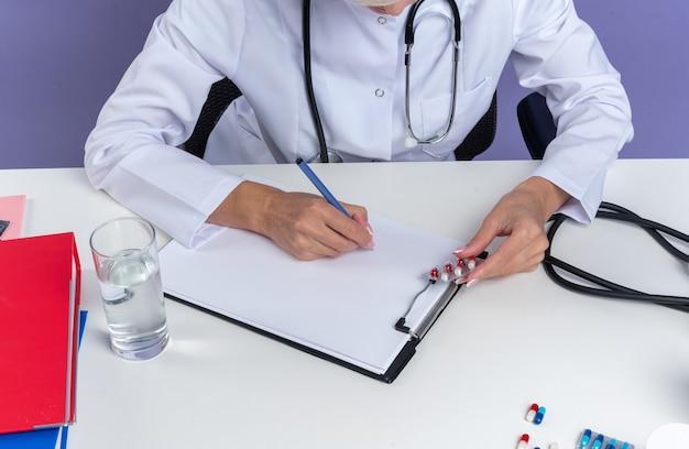 Zelfverzekerde volwassen slavische vrouwelijke arts in medische gewaad met stethoscoop zit aan bureau met office-hulpprogramma's schrijven op klembord met pen geïsoleerd op paarse achtergrond met kopie ruimte