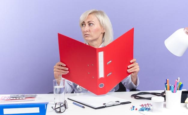 Zelfverzekerde volwassen slavische vrouwelijke arts in medische gewaad met stethoscoop zittend aan een bureau met office-hulpprogramma's houden bestandsmap en kijken naar kant geïsoleerd op paarse achtergrond met kopie ruimte