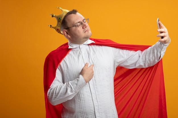 Zelfverzekerde volwassen superheld man in rode cape bril en kroon wijzend op zichzelf nemen selfie geïsoleerd op oranje muur