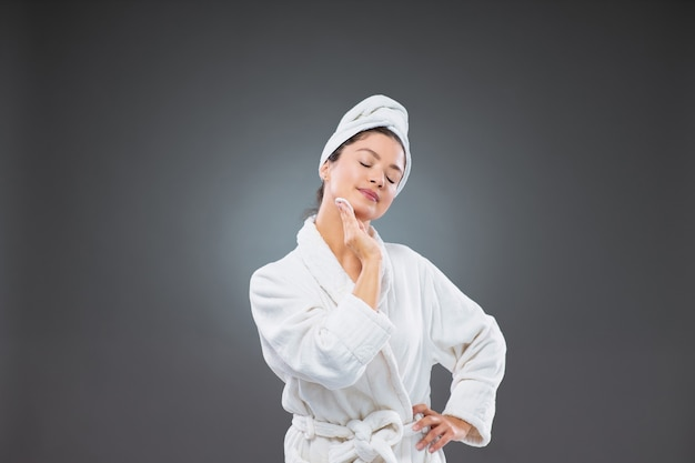 Zelfverzekerde volwassen vrouw in een badjas en een handdoek om haar hoofd gewikkeld met één hand, gebruik een wattenschijfje om haar gezicht en nek schoon te maken, terwijl de andere hand op haar heup leunt