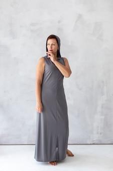 Zelfverzekerde volwassen vrouw in grijze jurk