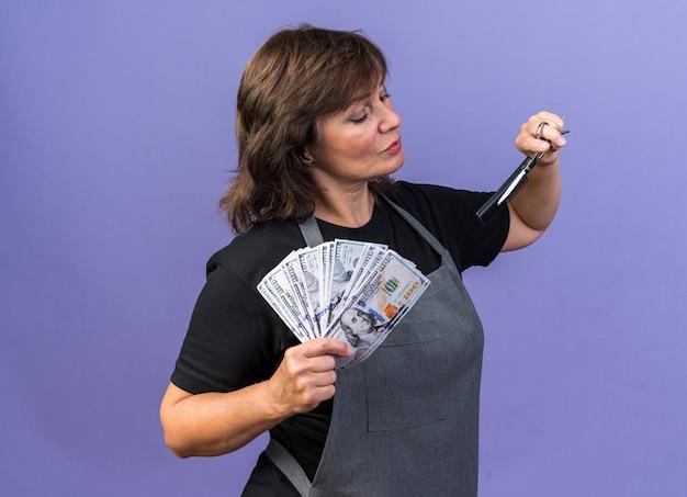 Zelfverzekerde volwassen vrouwelijke kapper in uniform die geld aanhoudt en kijkt naar kam en schaar geïsoleerd op paarse muur met kopieerruimte
