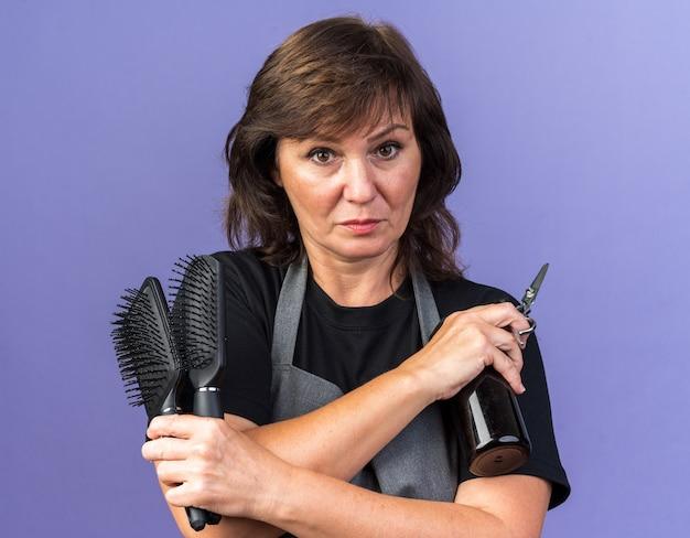 Zelfverzekerde volwassen vrouwelijke kapper in uniform met kammen spuitfles en schaar geïsoleerd op paarse muur met kopieerruimte