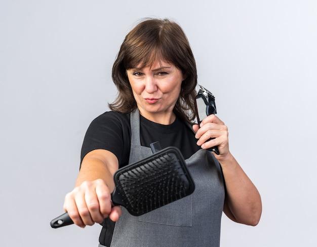 Zelfverzekerde volwassen vrouwelijke kapper in uniform met tondeuse en kam geïsoleerd op een witte muur met kopieerruimte
