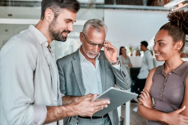 Zelfverzekerde volwassen zakenman in formele kleding die naar digitale tablet kijkt terwijl hij met collega staat co