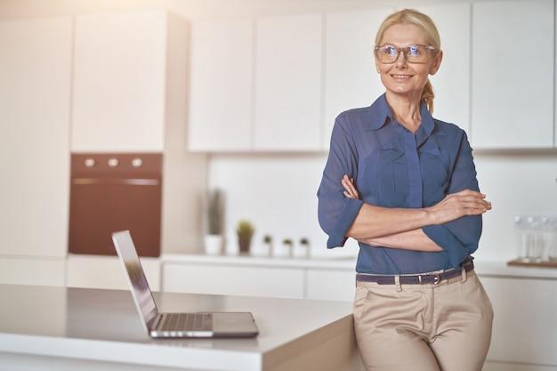 Zelfverzekerde volwassen zakenvrouw met een bril die glimlacht opzij terwijl ze thuis werkt met een laptop die staat met