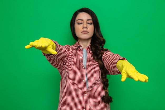 Zelfverzekerde, vrij blanke schonere vrouw met rubberen handschoenen die met gesloten ogen staan en haar handen uitstrekken