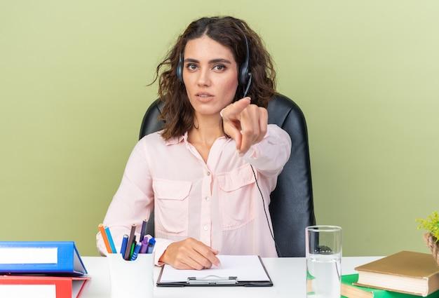 Zelfverzekerde, vrij blanke vrouwelijke callcenter-operator op een koptelefoon die aan het bureau zit met kantoorhulpmiddelen die op een groene muur wijzen