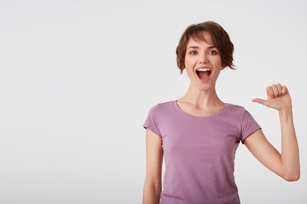 Zelfverzekerde vrolijke kortharige dame in een leeg t-shirt voelt trots op haar daden, wijst naar zichzelf, voelt een golf van trots, heft het hoofd op, glimlacht breed, draagt vrijetijdskleding, geïsoleerd over een witte muur.
