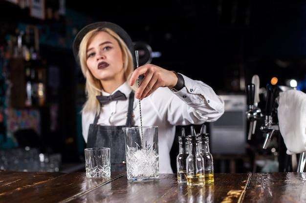 Zelfverzekerde vrouw bartending mengt een cocktail terwijl je in de buurt van de toog in de bar staat