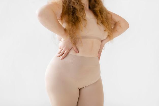 Zelfverzekerde vrouw die zich voordeed terwijl ze een bodyshaper draagt