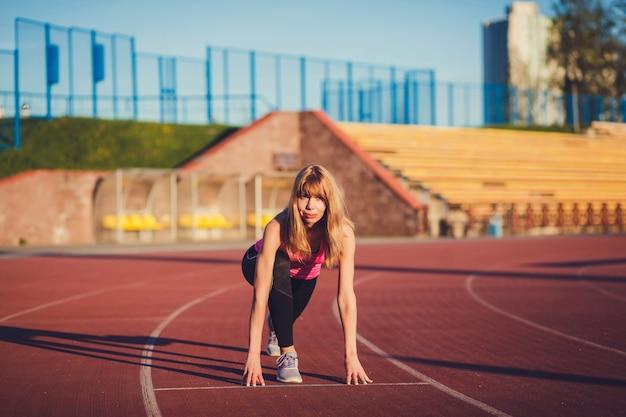 Zelfverzekerde vrouw in startpositie klaar om te rennen. vrouwelijke atleet die op het punt staat een sprint te starten en weg te kijken. Premium Foto