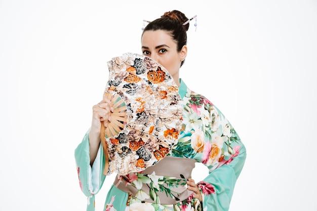 Zelfverzekerde vrouw in traditionele japanse kimono met handventilator die mond ermee op wit houdt?