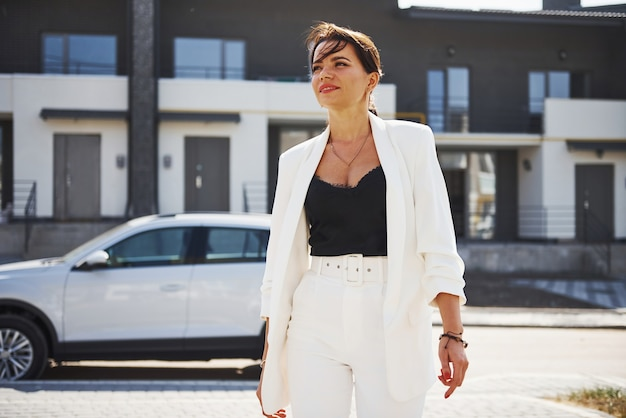 Zelfverzekerde vrouw in witte formele slijtage outdoots in de buurt van haar witte auto.