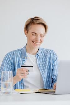 Zelfverzekerde vrouw met een laptop in het thuiskantoor die online winkelt