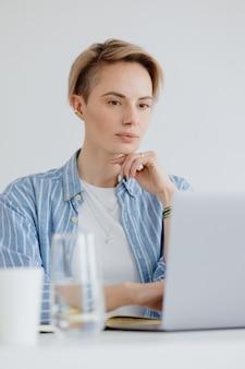 Zelfverzekerde vrouw met een laptop in het thuiskantoor werkt online of winkelt