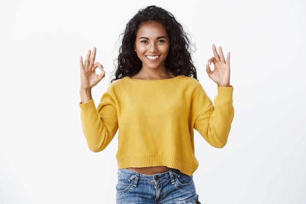 Zelfverzekerde vrouw met krullend haar in gele trui geeft positieve feedback, toont oké, goed, uitstekend gebaar glimlachend goedkeurend, tevreden kijkend
