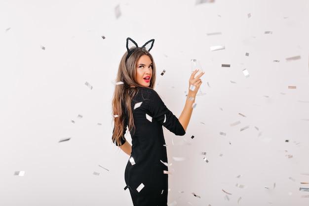 Zelfverzekerde vrouw met lang kapsel poseren onder confetti