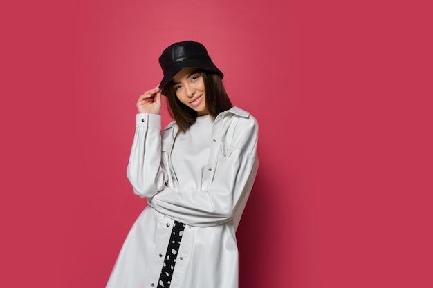 Zelfverzekerde vrouw met perfecte glimlach gekleed in stijlvolle pet en witte jas poseren op roze achtergrond. isoleren.