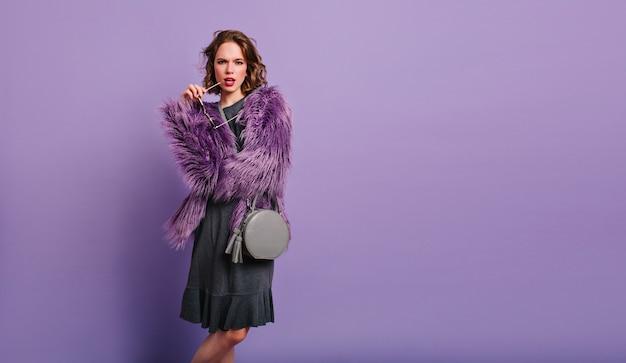Zelfverzekerde vrouw speels poseren in paarse bontjas