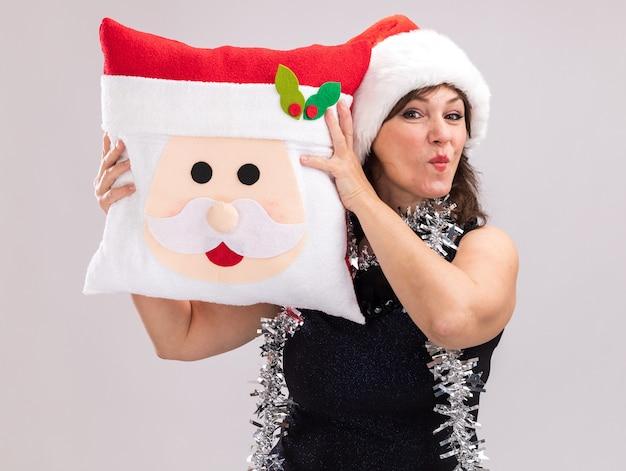 Zelfverzekerde vrouw van middelbare leeftijd dragen kerstmuts en klatergoud guirlande rond nek houden kussen van de kerstman hoofd aanraken met het kijken naar camera met samengeknepen lippen geïsoleerd op witte achtergrond