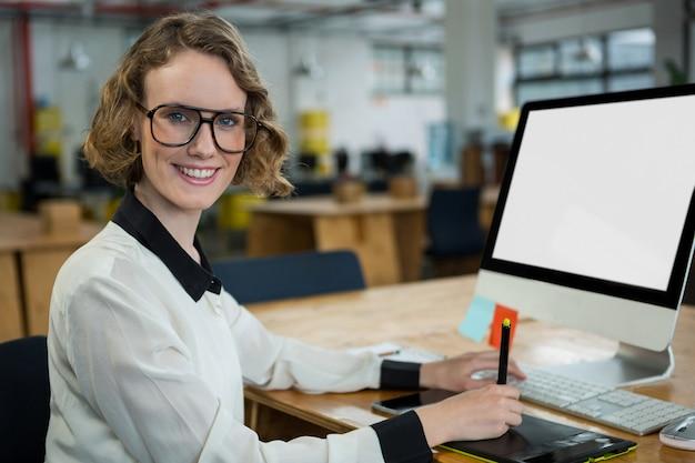 Zelfverzekerde vrouw zittend aan een bureau in kantoor