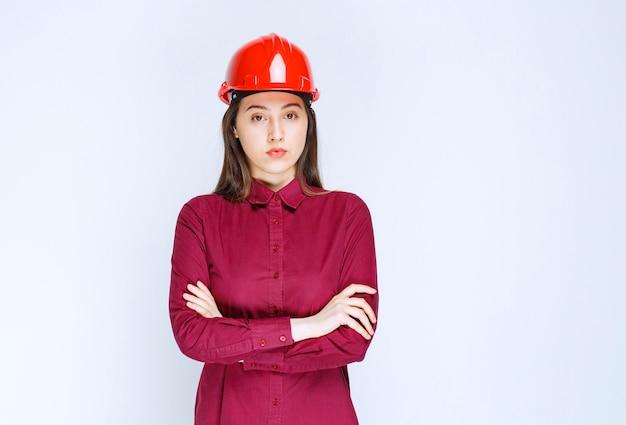 Zelfverzekerde vrouwelijke architect in rode harde helm die over de witte muur staat en zich voordeed.
