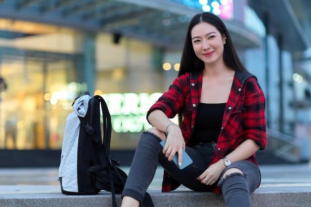 Zelfverzekerde vrouwelijke backpacker met rugzak zittend op trappen met mobiel voor mall