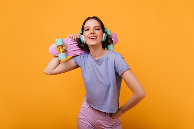 Zelfverzekerde vrouwelijke skateboarder die met geïnteresseerde glimlach kijkt. aangename bruinharige vrouw in hoofdtelefoons geïsoleerd.