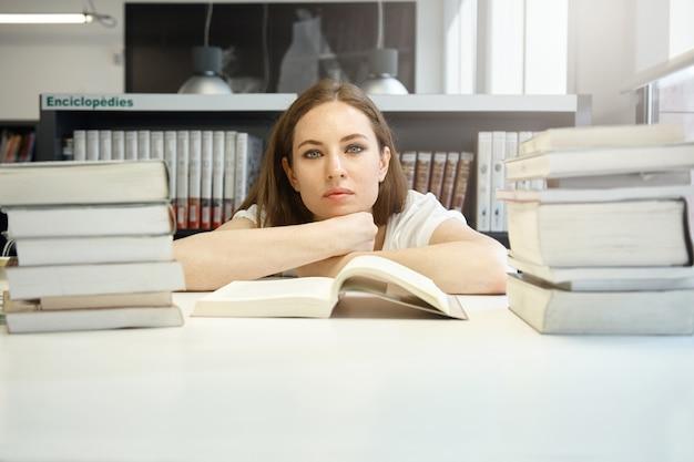 Zelfverzekerde vrouwelijke student studeert aan de bibliotheek, kijkt met een kalme gezichtsuitdrukking aan de tafel met haar kin op haar handen, leert vreemde talen, leest een leerboek