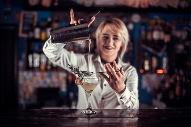 Zelfverzekerde vrouwentapster maakt een show en creëert een cocktail terwijl ze in de buurt van de toog in de bar staat