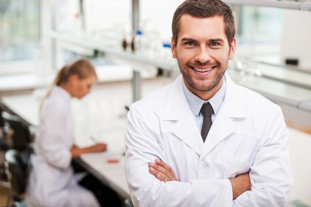 Zelfverzekerde wetenschapper. gelukkige jonge mannelijke wetenschapper die zijn armen gekruist houdt en naar de camera kijkt terwijl zijn vrouwelijke collega op de achtergrond werkt