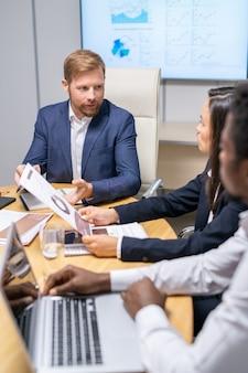 Zelfverzekerde zakenman die naar een van de twee collega's kijkt tijdens de bespreking van werkpunten