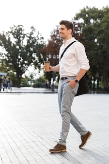 Zelfverzekerde zakenman gekleed in overhemd buiten lopen