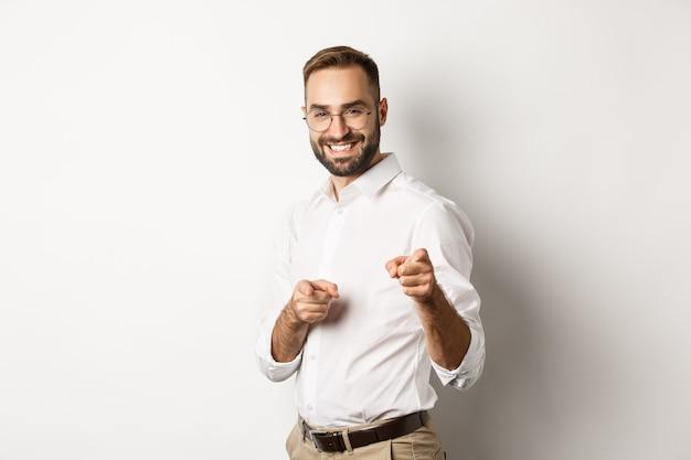 Zelfverzekerde zakenman glimlacht, wijst met de vingers naar je, gefeliciteerd of prijsgebaar, staande op een witte achtergrond