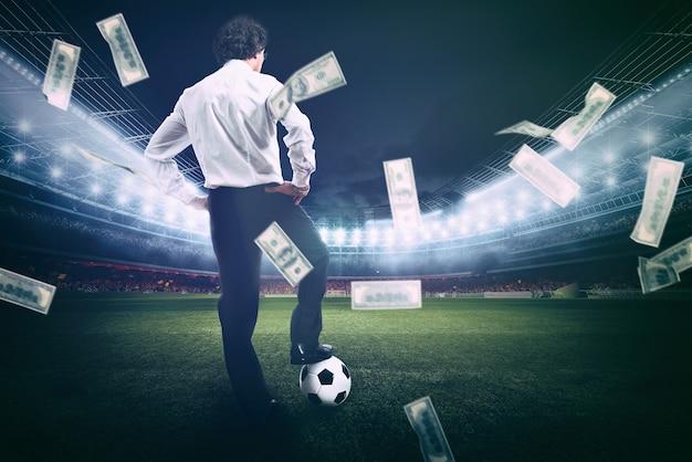 Zelfverzekerde zakenman in het midden van het voetbalveld verzamelt veel geld van het voetbal