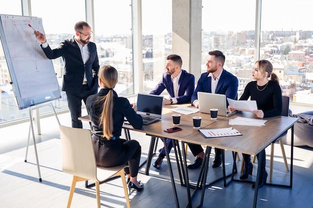 Zelfverzekerde zakenman maakt een presentatie van een nieuw project in de bestuurskamer tijdens een bedrijfsvergadering. mooie auditors praten met verschillende partners over het bedrijf aan de hand van een whiteboard en grafieken.