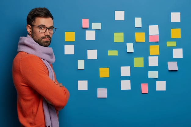 Zelfverzekerde zakenman of manager draagt warme sjaal en oranje trui, staat gekruiste armen tegen blauwe achtergrond