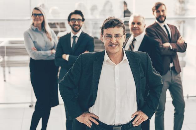 Zelfverzekerde zakenman op de achtergrond van een commercieel team. foto met kopie-ruimte