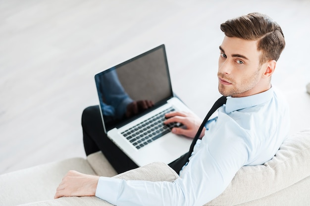 Zelfverzekerde zakenman op het werk. bovenaanzicht van zelfverzekerde jonge man die op laptop werkt