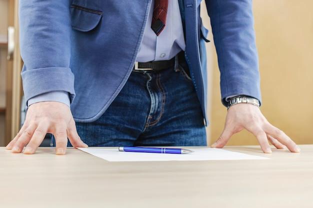 Zelfverzekerde zakenman poseren leunend op een tafel in een kantoor zakelijke onderhandelingen