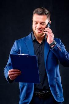 Zelfverzekerde zakenman praat aan de telefoon met map in hand geïsoleerd dan zwart