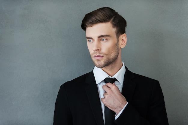 Zelfverzekerde zakenman. zelfverzekerde jonge zakenman die zijn stropdas aanpast en wegkijkt