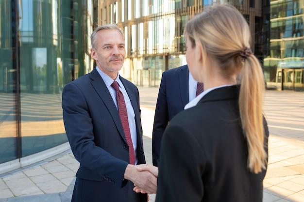 Zelfverzekerde zakenpartners staan in de buurt van kantoorgebouwen, handen schudden, ontmoeten en praten in de stad. contractbespreking en partnerschap concept