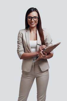 Zelfverzekerde zakenvrouw. aantrekkelijke jonge vrouw die naar de camera kijkt en glimlacht terwijl ze tegen een grijze achtergrond staat