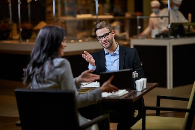 Zelfverzekerde zakenvrouw die de informatie op de tablet uitlegt terwijl de man er een twijfelachtig gebaar over maakt met de rechterhand