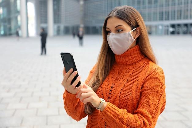 Zelfverzekerde zakenvrouw dragen beschermend gezichtsmasker bellen met telefoon terwijl staande in de buurt van modern kantoorgebouw buitenshuis